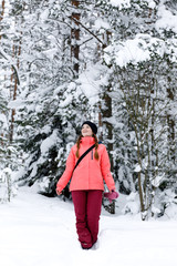 Smiling sport style girl in the winter forest