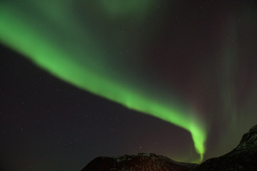 Bright green Northern Light (Aurora Borealis) lighting up the dark skies above the mountains, Tromsø, Norway