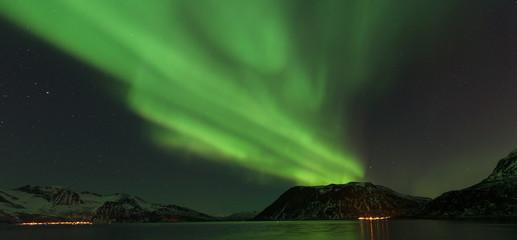 Bright green Northern Light (Aurora Borealis) lighting up the dark skies above the mountains, Tromsø, Norway