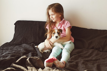 Home portrait of little girl hugging with puppy of Jack Russell Terrier dog on the bad against white wall