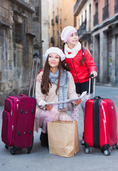 Cheerful girl and woman with map in scarf
