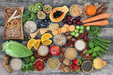 Foto auf Gartenposter Sortiment High dietary fibre health food concept with fruit, vegetables, whole wheat pasta, legumes, cereals, nuts and seeds with foods high in omega 3, antioxidants, anthocyanins, smart carbs and vitamins.