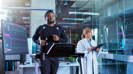 Male Athlete Walks on a Treadmill with Electrodes Attached to His Body while Sport Scientist Interacts with Touchscreen and Supervises EKG Status.