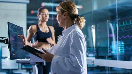 Sport Scientist Supervises Touches Display Showing EKG Status While in the Background Woman Athlete Running on a Treadmill with Electrodes Attached to His Body. Laboratory with High-Tech Equipment.