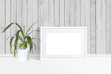 Blank photo frame mock up and yucca plant in flower pot near wooden wall