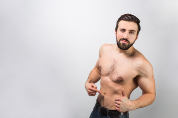 Good-looking and awesome guy is standing of a wall and pointing on himself and how his body is good. Young man is self-confident and loves himself quite much. Isolated on white background.