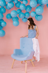 Beautiful girl in a blue dress in a pink room with blue balls and a blue armchair