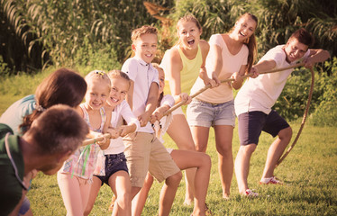 people with kids having fun outdoors pulling rope