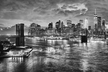 Black and white picture of the Brooklyn Bridge and the Manhattan at night, New York City, USA.