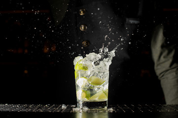 Glass filled with splashing fresh Caipirinha cocktail