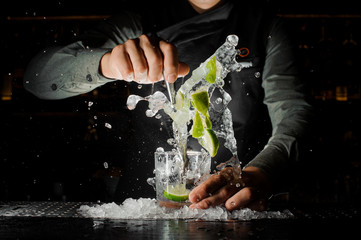 Barman hand squeezing fresh juice from lime making Caipirinha cocktail