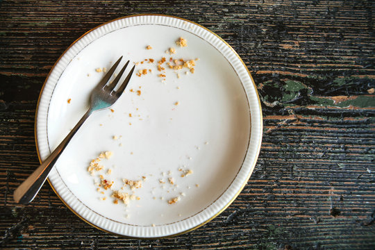 Conceptual image of the end of the holiday is an empty plate with crumbs and a fork on it.