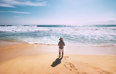 Little boy stay on ocean beach in sunny day