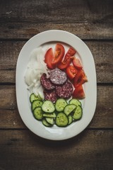 set of ingredients: sausage (salami), cucumbers, tomato, onions
