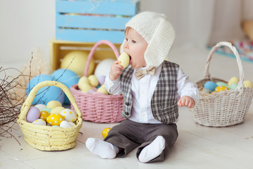Funny happy baby boy in bunny hat, tie bow and suit playing with Easter eggs. Eating egg