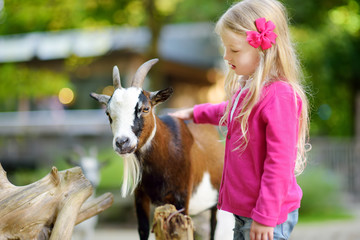 Cute little girl petting and feeding a goat at petting zoo. Child playing with a farm animal on sunny summer day. Wall mural
