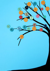 a man lays a tree out of colored buttons on a blue background