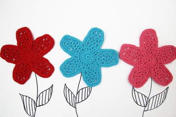 knitted flowers on a white background. view from above. children's background