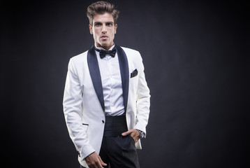 Businessman standing Stylish Luxury, elegant man in a white suit tuxedo with bow tie around his neck