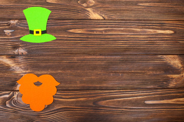 St. Patrick's Day theme colorful horizontal banner. Green leprechaun hat and shoe with gold on brown wooden background. Felt craft elements. Copy space. For greeting card,congratulation banner