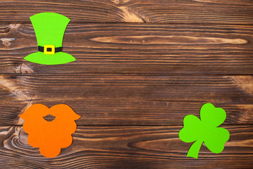 St. Patrick's Day theme colorful horizontal banner. Green leprechaun hat, beard and shamrock leaves on brown wooden background. Felt craft elements. Copy space. For greeting card, banner