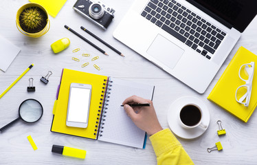 Workplace with office tools and gadgets. Cup of coffee on a table. Tablet, laptop, phone and camera to develop applications or other projects. White, black and yellow background. Flat layer photo.
