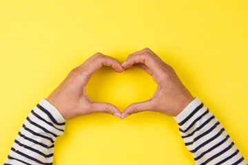 Woman hands making a heart shape on yellow background