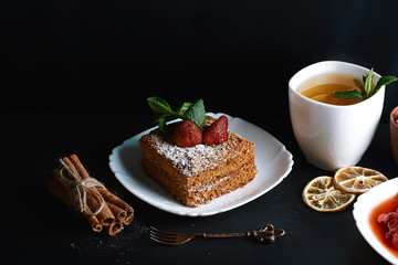 Slice of layered honey cake decorated with strawberry, dessert fork, mint, dried lemons, sticks of cinnamon, strawberry jam, cup of tea with lemon, close up, place for text, set