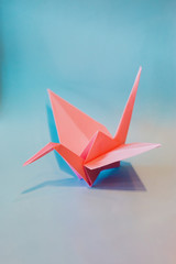 Colorful Origami birds flying to the light.