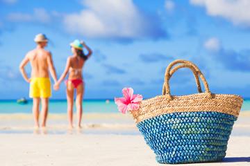 colourful straw beach bag abd hugging honeymoon couple on background