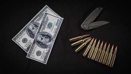 money, ammunition and a knife on a black background