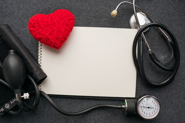 Medical mockup. White notebook, Red thread heart with tonometer on grey table. Sphygmomanometer, doctor workplace. Blood Pressure Monitor. Medical equipment. Cardiac diagnosis. Copy space