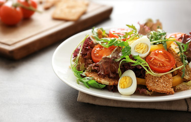 Salad with cherry tomatoes and quail eggs served on white plate, closeup