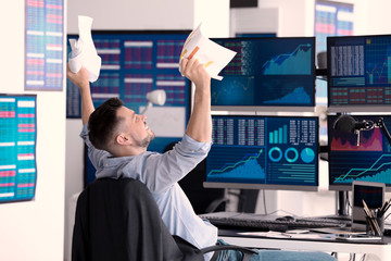 Emotional stock exchange trader with documents in office