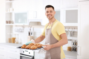 Man holding baking tray with delicious homemade croissants in kitchen