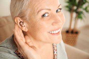 Mature woman with hearing aid, closeup