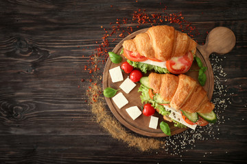 Wooden board with tasty croissant sandwiches on table