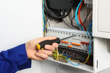 Young electrician repairing distribution board, closeup