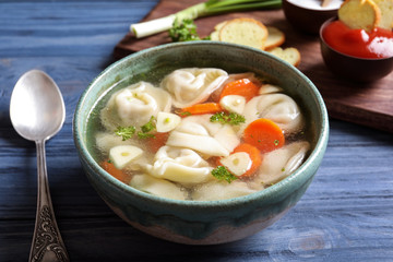 Bowl of delicious soup with dumplings on table