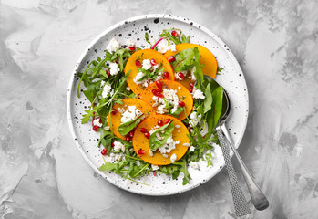 Tasty persimmon with cottage cheese and arugula on plate