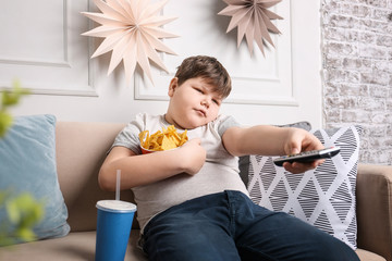 Overweight boy watching TV with snacks indoors