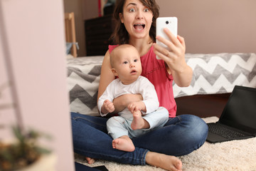 Young mother taking selfie with her cute baby at home