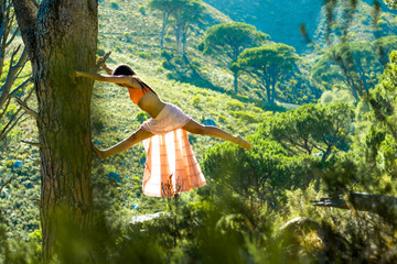 Woman climbing a tree in a forest dancing with Table Mountain in the background.