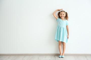 Little girl measuring height near light wall
