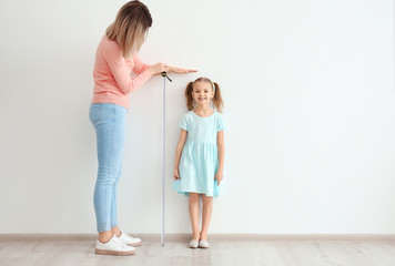 Mother measuring height of little girl near light wall