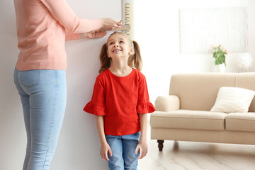 Mother measuring height of little girl near door