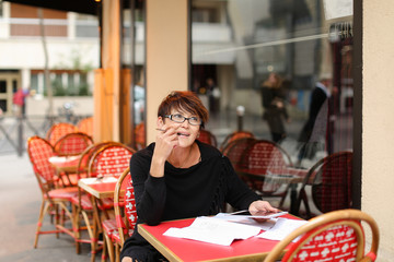 Business woman sitting at table in street cafe, fill declaration with tablet and sheets of paper. Lady dressed in black blouse have contented expression. Female hold white gadget and pen, comp