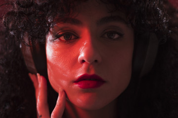 Curly woman with headphones in studio