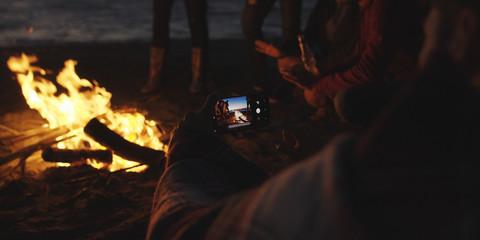 Couple taking photos beside campfire on beach