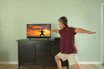 Man doing Warrior 2 yoga pose while watching a yoga class video that was taped during sunrise on the beach on tv or computer monitor at home showing people can train anywhere now with the internet.